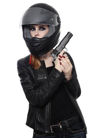 Hermosa chica rubia sexy elegante casco de motociclista con pistola sobre fondo blanco Foto de archivo