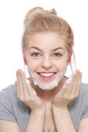 Portrait of young beautiful happy smiling young blond girl cleaning her face with foam over white background