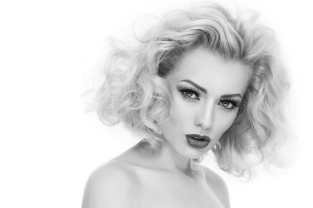 Black and white portrait of young beautiful woman with blond curly hair and false eyelashes over white background Stock Photo - 27690107