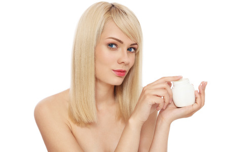 Young beautiful healthy blond woman with pot of face cream over white background Stock Photo - 27690106