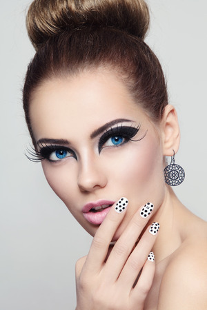 Portrait of young beautiful woman with stylish cat eye make-up and fancy polka dot manicure photo