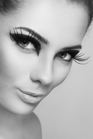 pesta�as postizas: Close-up retrato en blanco y negro de la joven y bella mujer con estilo de maquillaje y enormes pesta�as postizas