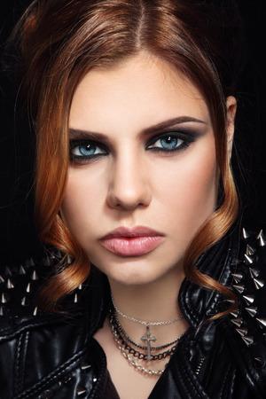 �spiked: Retrato de mujer joven y hermosa en la chaqueta de cuero con pinchos