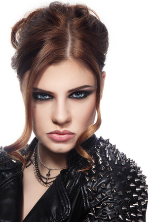 Portrait of young beautiful woman in spiked leather jacket over white  photo