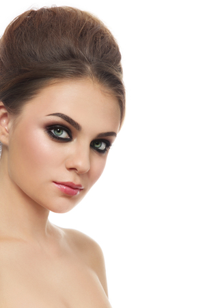 smoky eyes: Portrait of young beautiful woman with smoky eyes and hair bun over white , copy space  Stock Photo