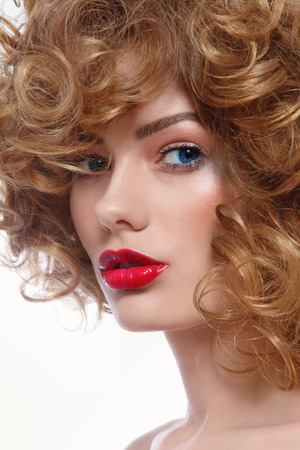 perming: Portrait of young beautiful blue-eyed woman with curly hair and red lipstick