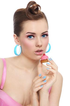 guilty pleasure: Retrato de joven bella mujer sexy con el petit four pasteler�a en la mano m�s de blanco