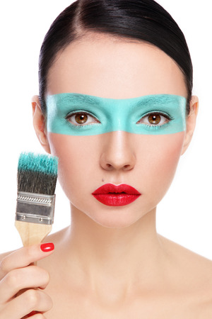 retouch: Young beautiful woman with painting brush and paint on her face over white  Stock Photo