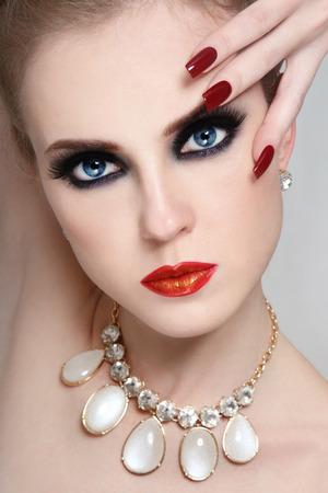 uñas largas: Retrato de joven hermosa mujer glamorosa con los ojos ahumados y las uñas largas