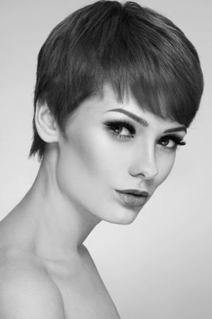 woman hairstyle: Black and white portrait of young beautiful woman with stylish short haircut and extended lashes