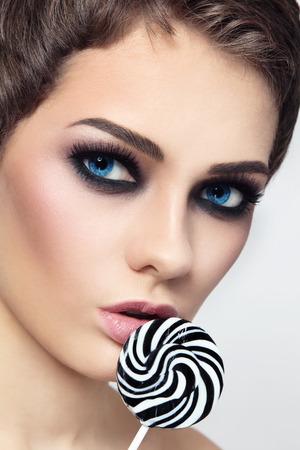 lentes de contacto: Close-up retrato de la joven morena de ojos azules hermosa con los ojos ahumados y piruletas rayas de fantasía en la mano