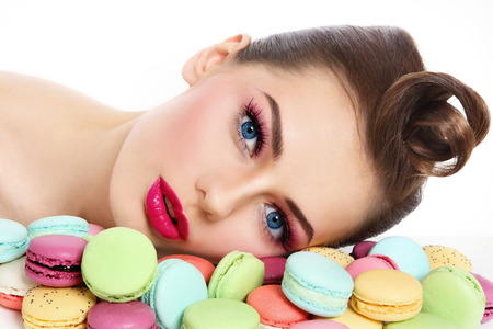 guilty pleasure: Portrait of young beautiful woman with colorful macaroons over white