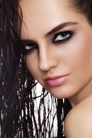 Close-up portrait of young beautiful tanned woman with dewy skin and smoky eyes photo