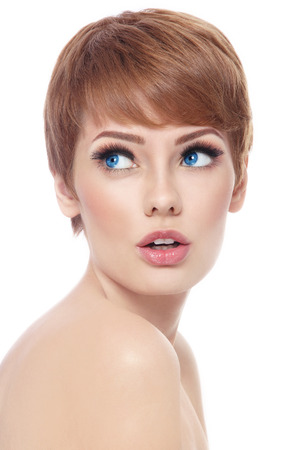 short haircut: Young beautiful woman with stylish short haircut and fresh make-up looking upwards with interest over white  Stock Photo