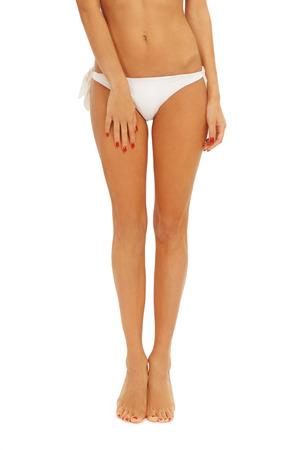 piernas sexys: Piernas largas y bronceadas de la joven mujer sexy en bikini sobre fondo blanco