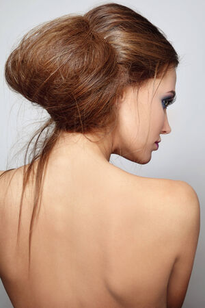 messy hairstyle: Young beautiful woman with stylish hair bun Stock Photo