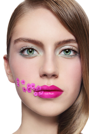 Close-up portrait of young beautiful girl with fuchsia lipstick and small pink flowers on her face, over white background photo
