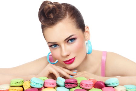 guilty pleasure: Young beautiful woman with colorful macaroons over white background