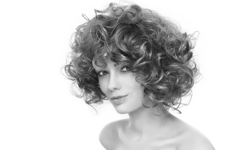permanent wave: Black and white portrait of young beautiful healthy woman with stylish curly hairdo over white background
