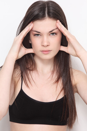 cephalgia: Young beautiful slim girl with headache expression