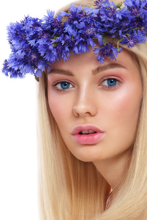 anti ageing: Young beautiful fresh girl with wreath of blue cornflowers on her head over white background Stock Photo