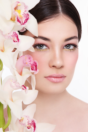 anti ageing: Close-up portrait of young beautiful woman with white orchid Stock Photo
