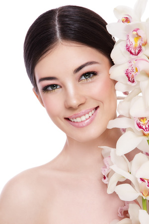 anti ageing: Young beautiful healthy smiling happy woman with white orchid over white background Stock Photo