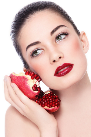 anti ageing: Portrait of young beautiful woman with pomegranates in her hand over white background Stock Photo