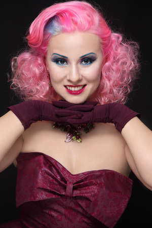 perming: Smiling happy vintage beauty with pink curly hair and fancy make-up Stock Photo