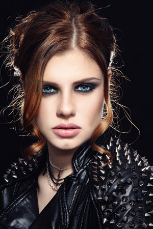 spiked: Portrait of young beautiful woman with stylish make-up in spiked leather jacket