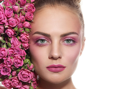 anti ageing: Close-up horizontal portrait of young beautiful girl with fresh make-up and pink roses over white background, copy space Stock Photo