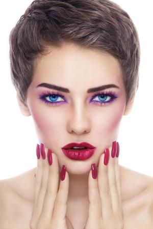 unas largas: Retrato de joven bella mujer con estilo de maquillaje y uñas largas sobre fondo blanco Foto de archivo