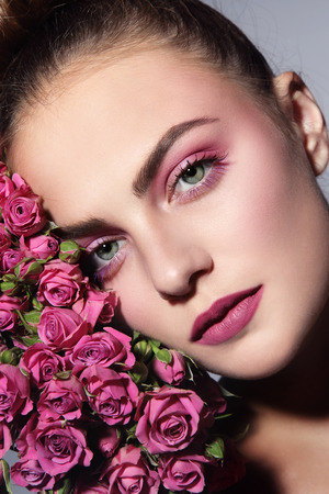 anti ageing: Close-up portrait of young beautiful woman with pink roses Stock Photo