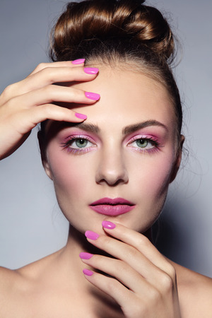 pink nail polish: Portrait of young beautiful girl with stylifh hairdo, make-up and manicure Stock Photo