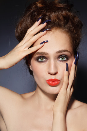 Young beautiful woman with stylish hairdo, long nails, bright lips and funny expression photo