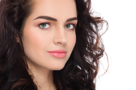 Close-up portrait of young beautiful woman with fresh clean make-up and curly hair over white background Standard-Bild