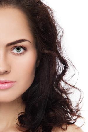 Primer plano retrato de mujer joven y hermosa con fresca y limpia el maquillaje y el pelo rizado sobre fondo blanco