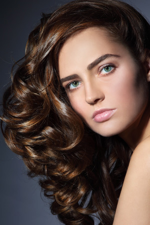 perming: Portrait of young beautiful woman with healthy long curly hair