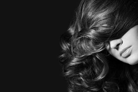 Black and white shot of woman with long curly hair photo