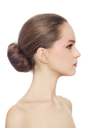 Profile portrait of young beautiful girl with hair bun over white background photo