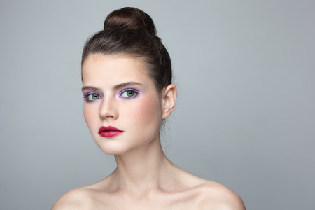 Portrait of young beautiful woman with stylish make-up and hair bun photo