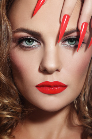 long nails: Close-up portrait of young beautiful woman with red lipstick and long stiletto nails