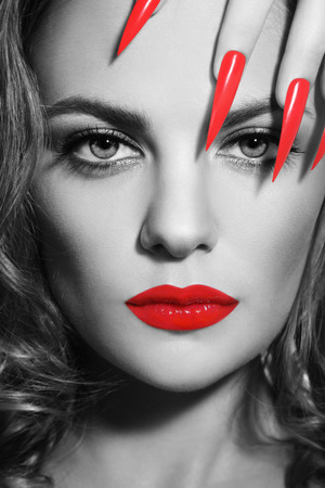 Close-up monochrome portrait of young beautiful woman with red lipstick and long stiletto nails