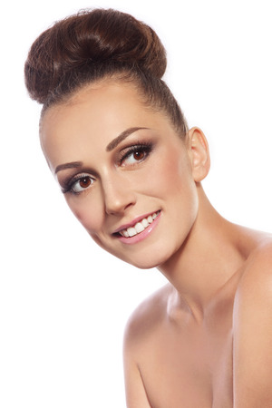 false teeth: Young slim attractive smiling woman with stylish hair bun over white background