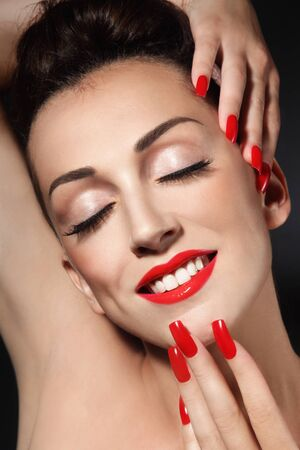 fake eyelashes: Portrait of young beautiful smiling girl with long red nails and lipstick