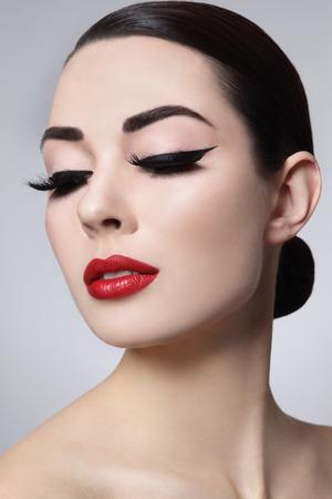 Portrait der jungen schönen Frau mit stilvollen Make-up. Falsche Wimpern, schwarzen Eyeliner und rote Lippen