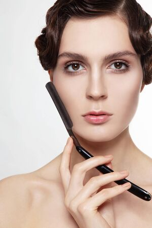 facelift: Beautiful young woman with cold wave hairdo and vintage razor in her hand Stock Photo