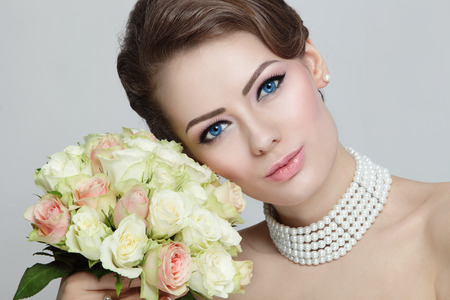 Close-up portrait of young beautiful bride with stylish make-up and hairdo holding bouquet photo