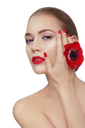 nailpolish: Young beautiful woman with clean make-up, red lips, fancy manicure and red flower in her hand over white background