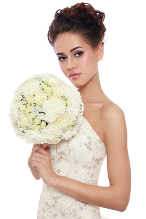 Young beautiful slim bride with stylish make-up and hairdo holding bouquet in her hand over white background photo